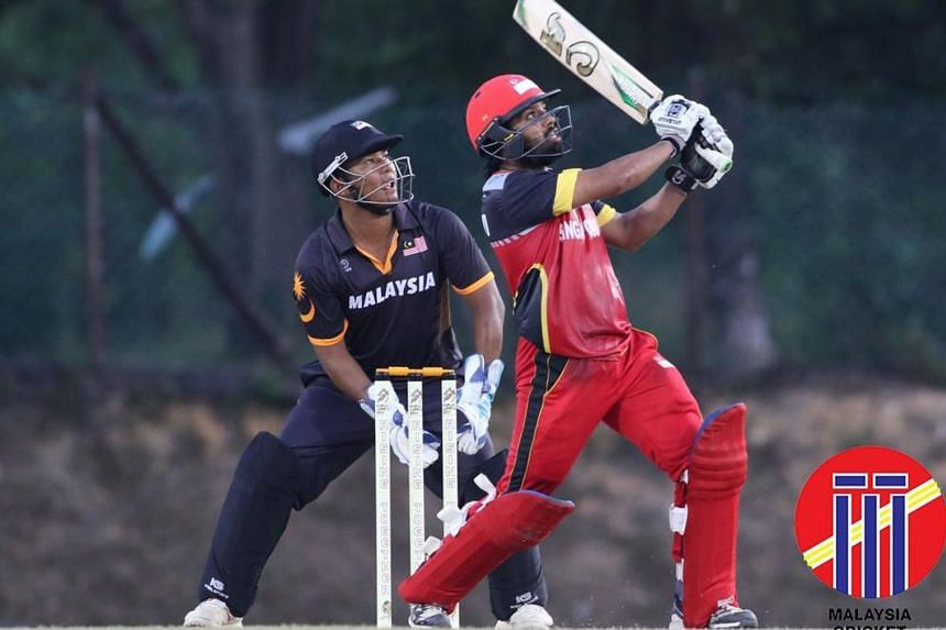 Singapore's Rezza Gaznavi, the team's highest scorer with 86 not out, hitting a shot as Malaysian wicket-keeper Shafiq Sharif watches during their match on Aug 23, 2017.