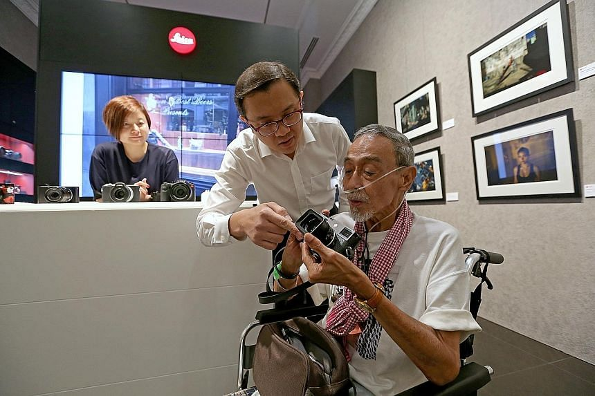 Freelance photographer Alan Lee, who is suffering from a lung disease, checking out a Leica camera with the help of store manager Ray Tan at the Leica Store Singapore in Fullerton Hotel yesterday. Getting Mr Lee out of Assisi Hospice proved to be a c