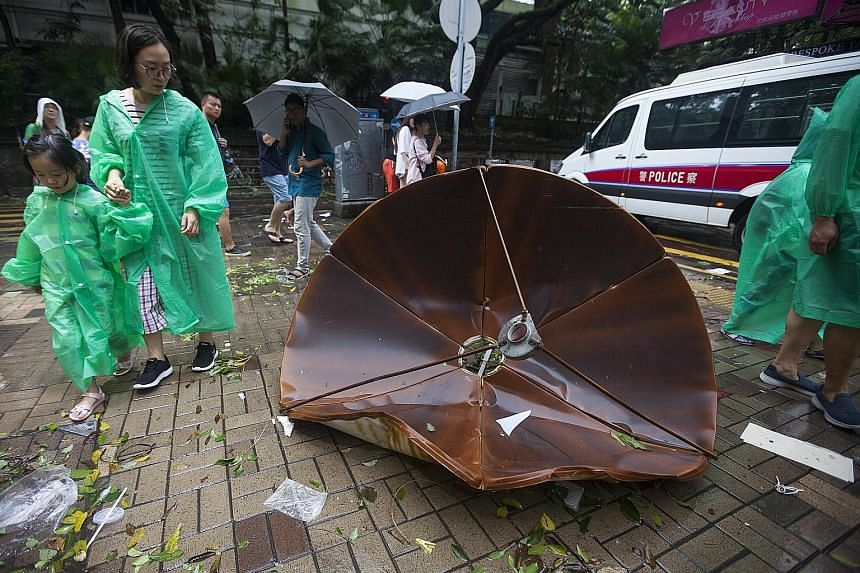 A satellite dish was blown off a rooftop onto the sidewalk in Tsim Sha Tsui, Hong Kong, yesterday. Residents cleaning up the debris at a public housing estate in the district of Heng Fa Chuen, in Hong Kong, after Typhoon Hato swept across the city ye