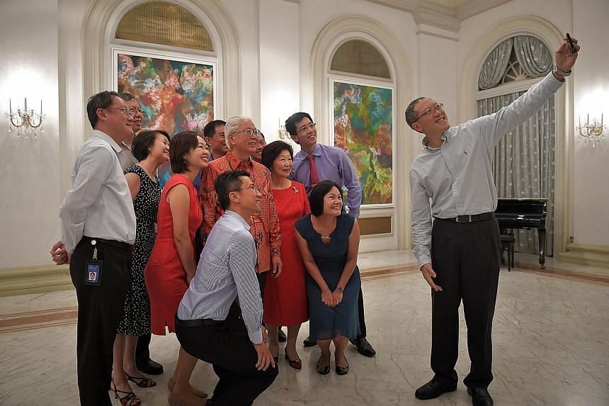 President Tony Tan Keng Yam and Mrs Mary Tan having a wefie taken with current and former staff of the President's Office and public agencies that have assisted them. The person taking the wefie is Mr Chew Hock Yong, Permanent Secretary at the Minist