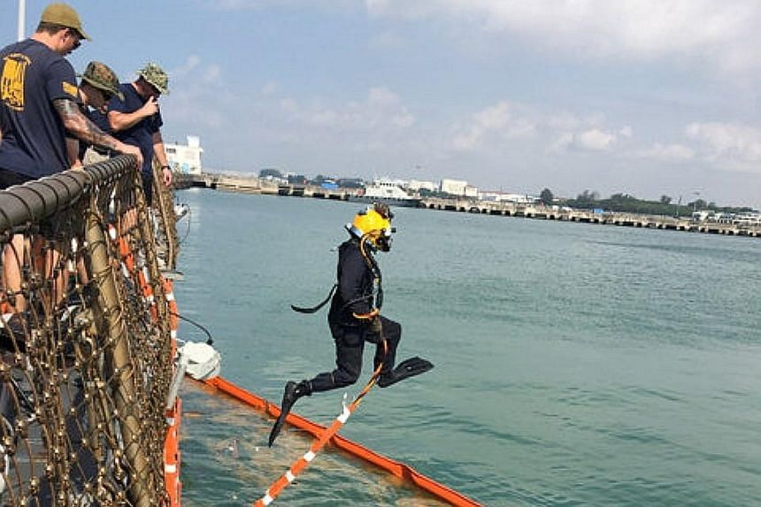 The USS John S. McCain at Changi Naval Base yesterday, where divers from the US military have been providing support to the ship.
