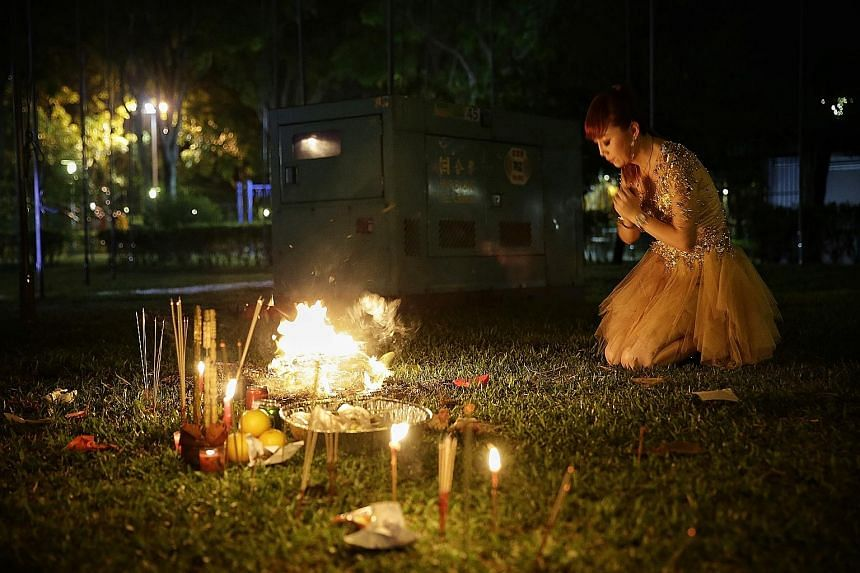 Getai singer Yuan Jin burning joss paper before she takes the stage at a getai performance at an open field in Yung An Road. The Hungry Ghost Festival, which takes place in the seventh month of the lunar calendar, officially started on Tuesday. Durin