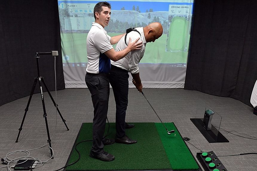 GolfTEC Singapore centre manager Craig Crandall demonstrating how GolfTEC's motion measurement technology works to improve a golfer's swing, with Pro Golf Asia executive director Abhinav Gorawara acting as a student. The Republic Plaza II facility is