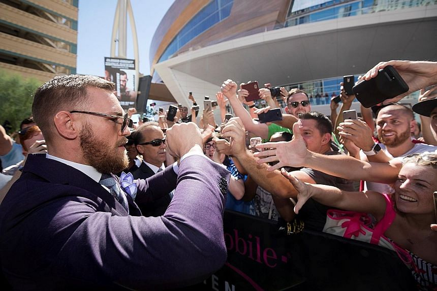 UFC lightweight champion Conor McGregor of Ireland greeting his rabid fans in Las Vegas as the MMA star gears up for Saturday's boxing super-fight against undefeated American boxer Floyd Mayweather (below).