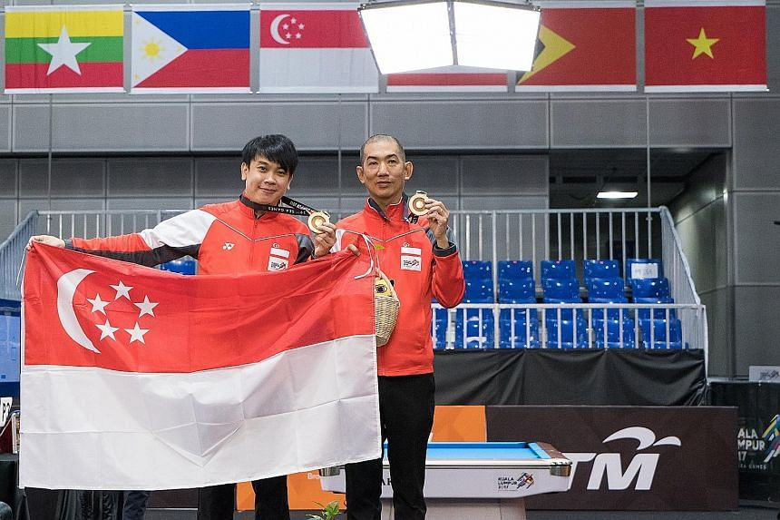 Above: Chan Keng Kwang (left) and Tey Choon Kiat hold up their gold medals after defeating their Thai opponents in the snooker doubles final. Left: Tey lining up a shot in the final. The 49-year-old said experiences in previous Games helped the pair