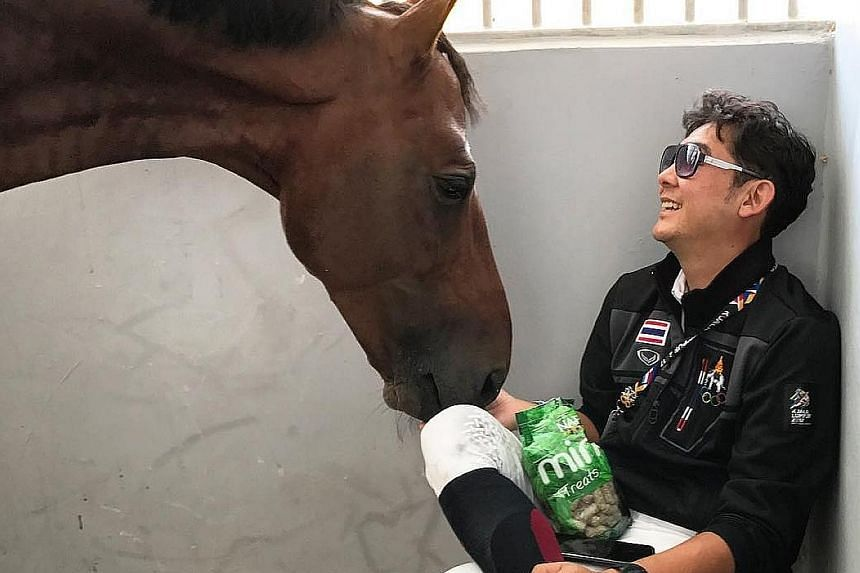 Chalermcharn Yotviriyapanit, Thailand's dressage team silver medallist, giving his ride a treat, surely something it won't say neigh to.