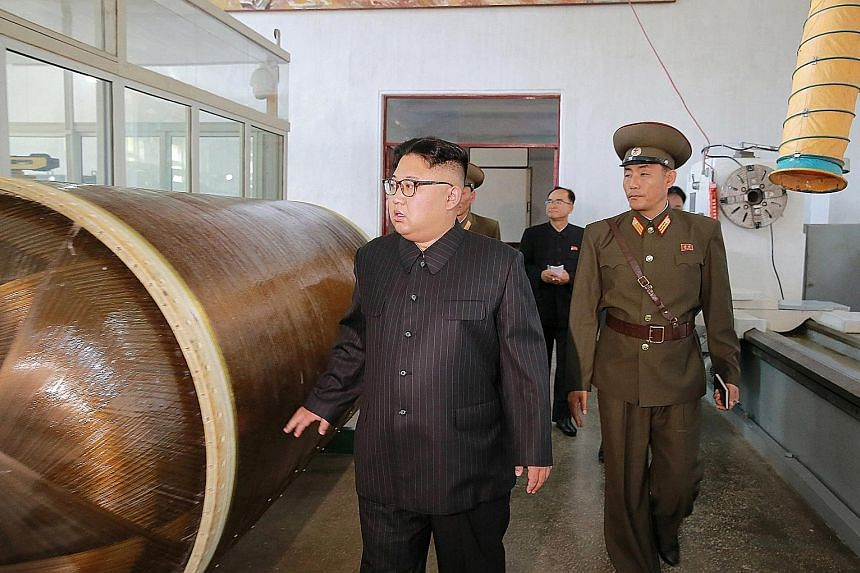 Mr Kim Jong Un being briefed on intercontinental ballistic missile warhead tips and solid-fuel rocket engines during a tour of the Chemical Material Institute of the Academy of Defence Science in North Korea.