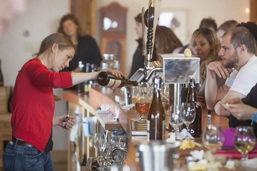 Ms Melissa Madden pours a customer's drink at Finger Lakes Cider House in Interlaken, New York, in March 2017.