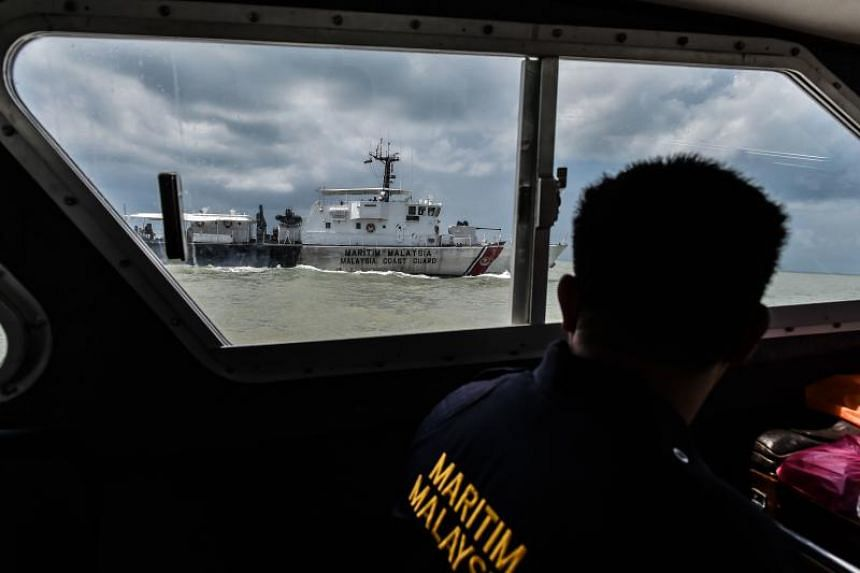 A member of the Malaysian Maritime Enforcement Agency taking part in the rescue operation for the missing sailors from the USS John S. McCain off the Johor coast.