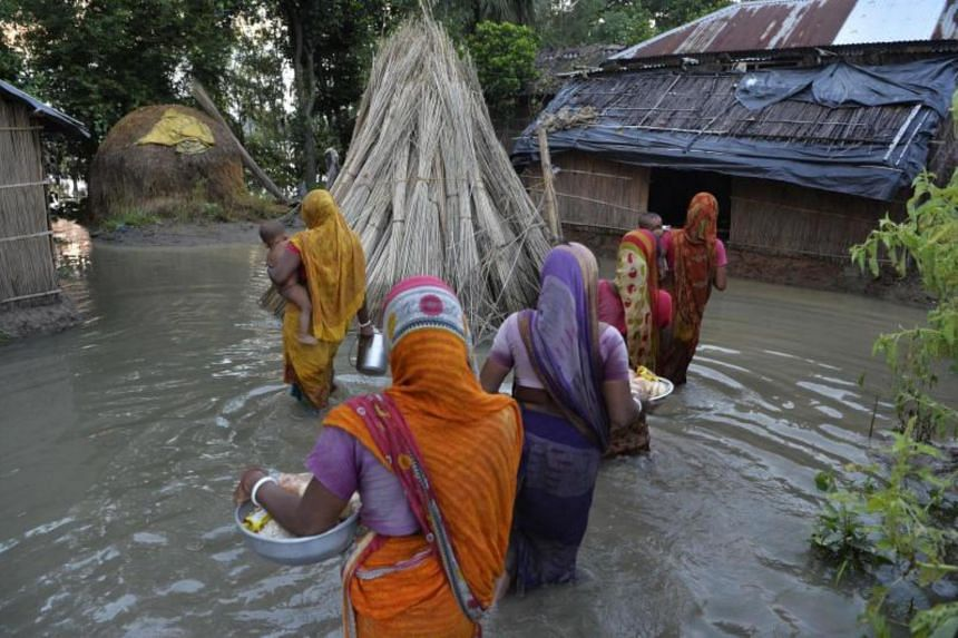 Indian villagers wading through floodwaters after collecting relief supplies, in Gazole village, Malda district, West Bengal on Aug 22, 2017.
