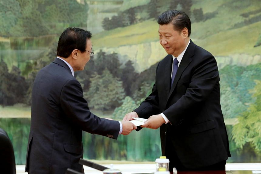 South Korean special envoy Lee Hae Chan (left) passes on a hand-written letter from South Korean President Moon Jae In to Chinese President Xi Jinping during a meeting at the Great Hall of the People in Beijing.