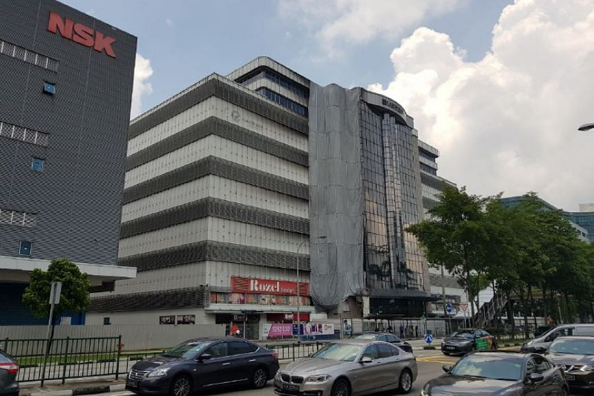 On Wednesday, ST found that the cladding panels at 30 Toh Guan Road (pictured) had been removed. This was carried out some time last month, said tenants, adding that they were assured by the building management that the building is safe for occupatio