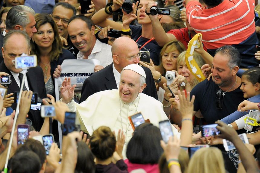 Pope Francis (centre) arriving for his weekly audience at the Vatican.