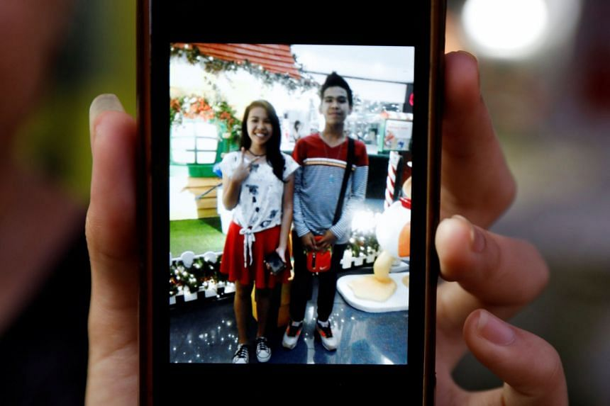 Kian Loyd's sister Shirley shows a photo of herself and her brother on a cellphone.