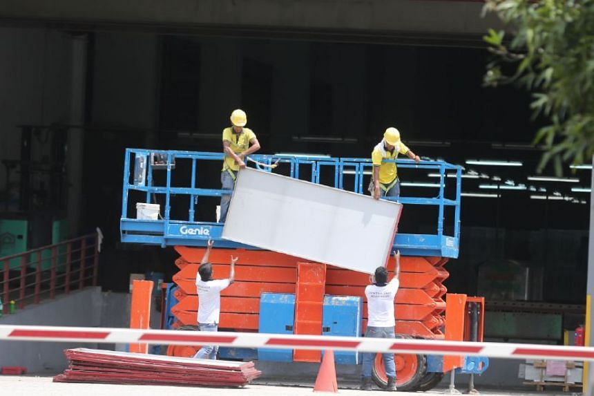 Workers remove the cladding on 3, Pioneer Sector 3, on Aug 25, 2017.