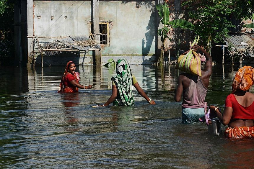 Villagers making their way through floodwaters at Alal village in Malda district, in the Indian state of West Bengal on Wednesday. So far, 152 people have died in the low-lying state.