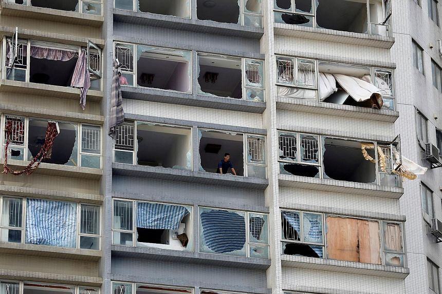 A vehicle swept into an awkward position and a damaged apartment block in the aftermath of Typhoon Hato yesterday in Macau, where the death toll stood at eight. In the neighbouring southern Chinese province of Guangdong, at least eight people died, s