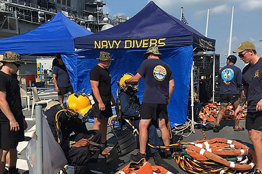 US Navy and Marine Corps divers providing support to USS John S. McCain at Changi Naval Base on Wednesday. Search efforts will now be mostly focused on the damaged destroyer.