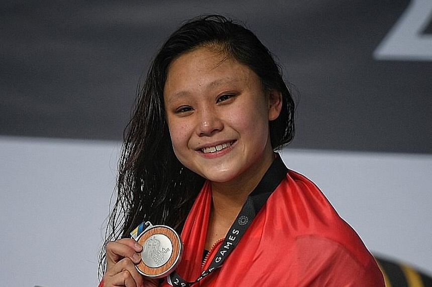 Above: An exuberant Quah Zheng Wen celebrates after winning gold in the 100m men's backstroke after trailing Indonesia's I Gede Siman Sudartawa, who defeated him in the 50m backstroke. Left: Samantha Yeo after taking the silver medal in the 200m indi