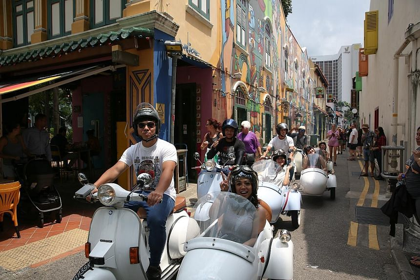 Philippine tourist Mary Grace Lucero on a Vespa tour of Kampong Glam yesterday. Among the new tours on offer are Vespa rides in locations such as Joo Chiat and Little India, as well as a walking tour of next-generation hawkers.