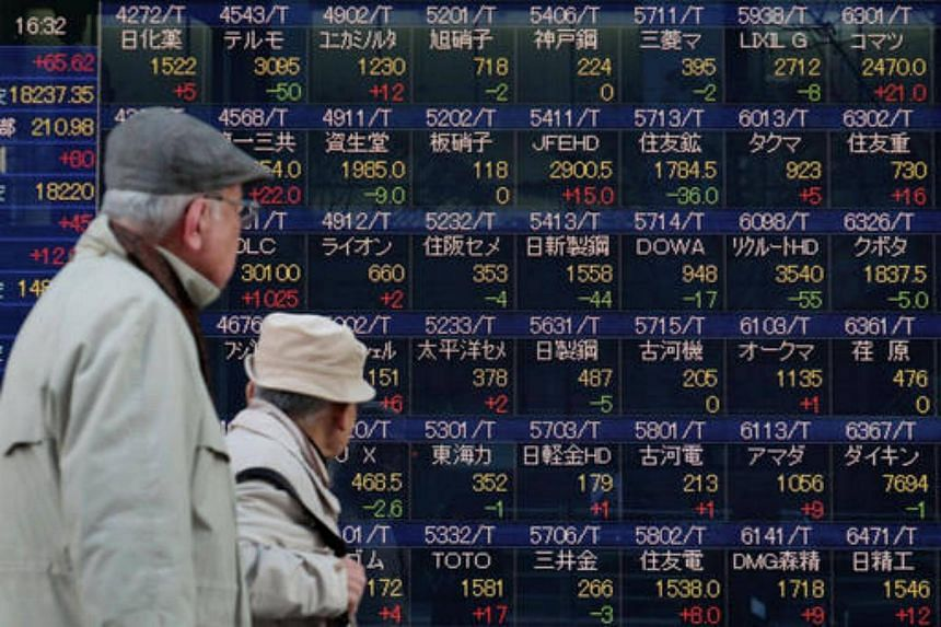 Pedestrians walk past an electronic stock board outside a securities firm in Tokyo, Japan.
