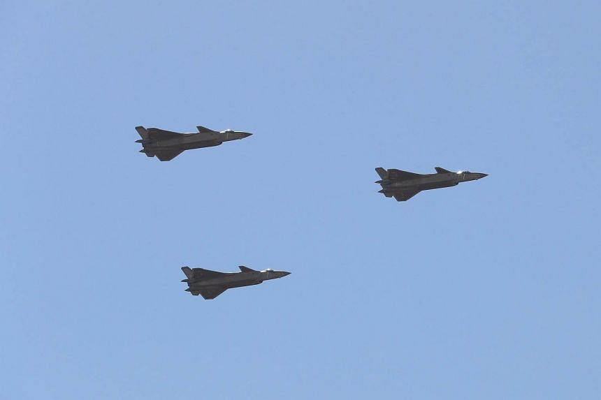 Chinese J-20 stealth fighter jets fly past during a military parade at the Zhurihe training base on July 30, 2017.