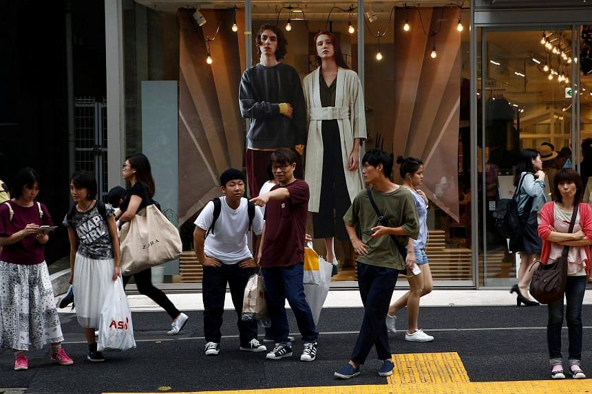People stand in front of a shop's advertisement board at a shopping district in Tokyo.