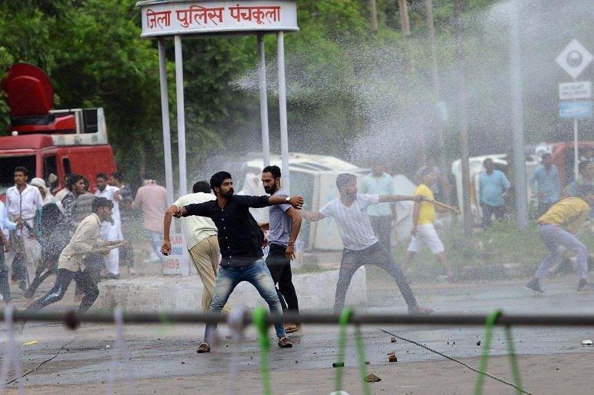 Supporters of Indian religious leader Gurmeet Ram Rahim Singh throw stones at security forces as they are sprayed with a water cannon in Panchkula on Aug 25, 2017.