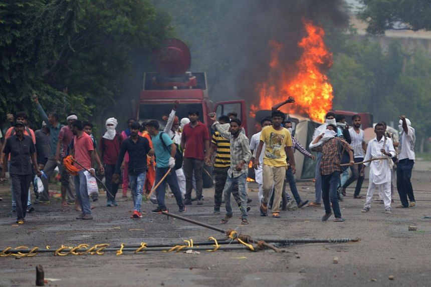 Supporters of Indian religious leader Gurmeet Ram Rahim Singh throw stones at security forces next to burning vehicles during clashes in Panchkula on Aug 25, 2017.