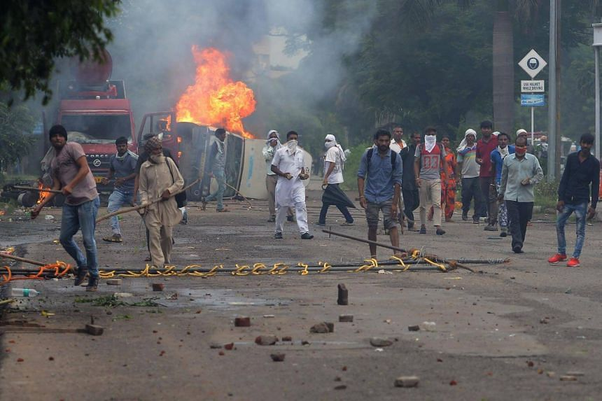 Supporters of Indian religious leader Gurmeet Ram Rahim Singh clash with security forces next to burning vehicles in Panchkula on Aug 25, 2017.