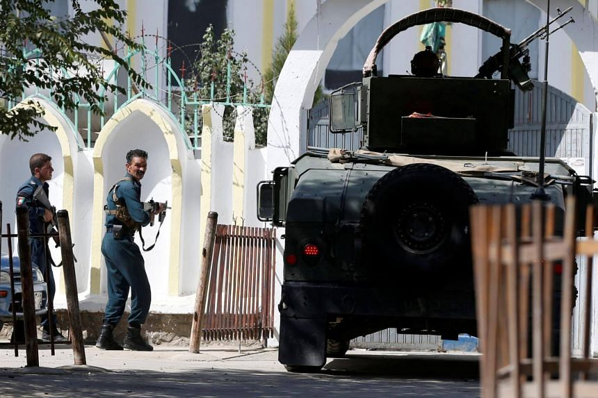 Afghan policemen take position at the site of a suicide attack followed by a clash between Afghan forces and insurgents after an attack on a Shi'ite Muslim mosque in Kabul, Afghanistan on Aug 25, 2017.