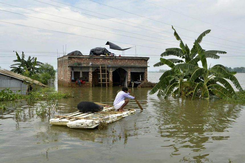 A villager using a makeshift raft outside his partially flooded house at Chachol village in the Indian state of West Bengal on Aug 23, 2017.