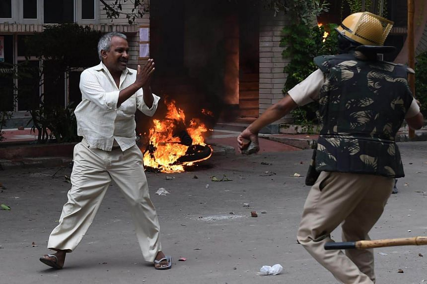 A follower of Indian religious leader Gurmeet Ram Rahim Singh pleads for his safety after being hit with a stick during clashes in Panchkula on Aug 25, 2017.