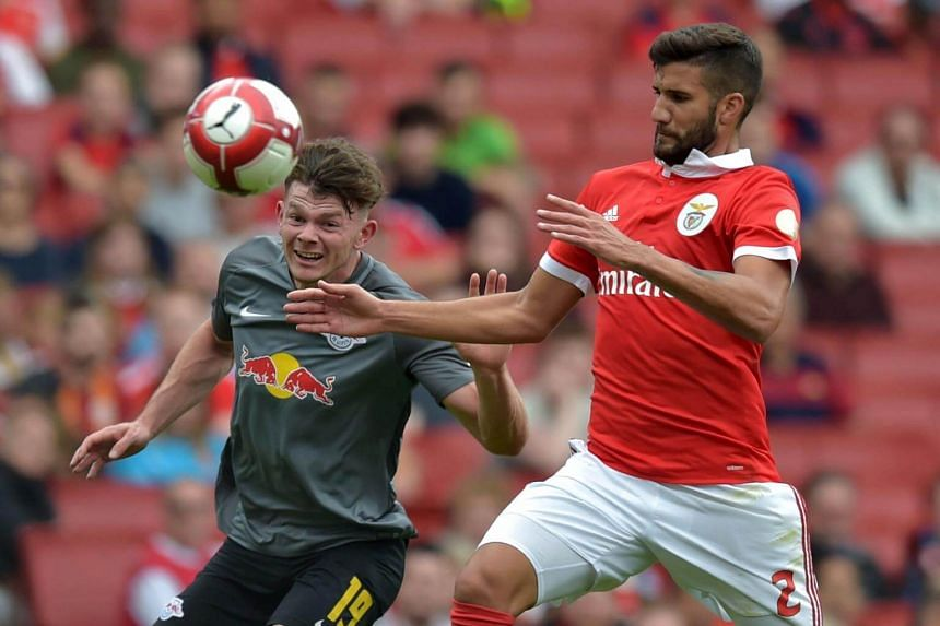 Oliver Burke (left) vies with Benfica's Lisandro Lopez during a pre-season friendly football match at The Emirates Stadium on July 30, 2017.