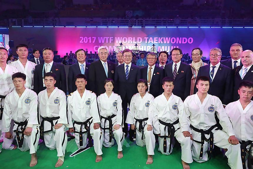 South Korean President Moon Jae-in (centre) posing with North Korean Taekwondo Demonstraition team during the opening ceremony of the World Taekwondo Championships in the southern county of Muju on  June 24, 2017.