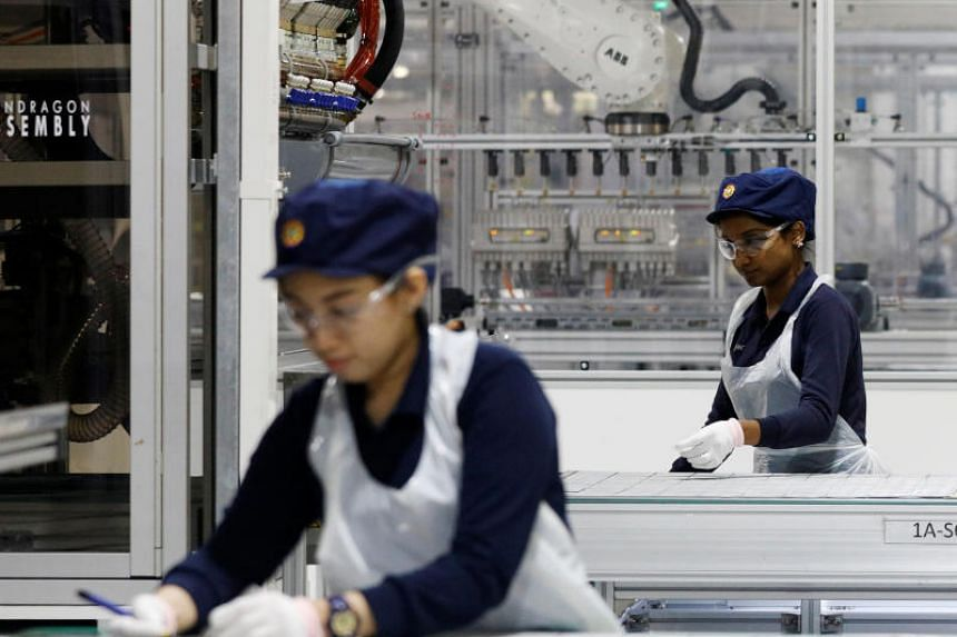 Employees work at a production line at an REC solar panel manufacturing plant in Singapore.