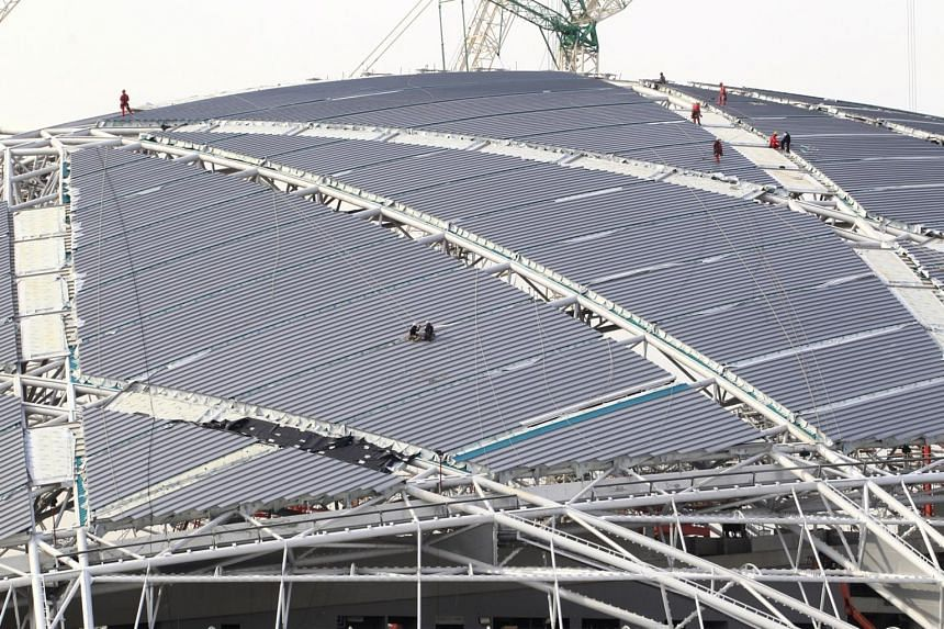 Workers installing cladding on a section of the roof of the Singapore Sports Hub.