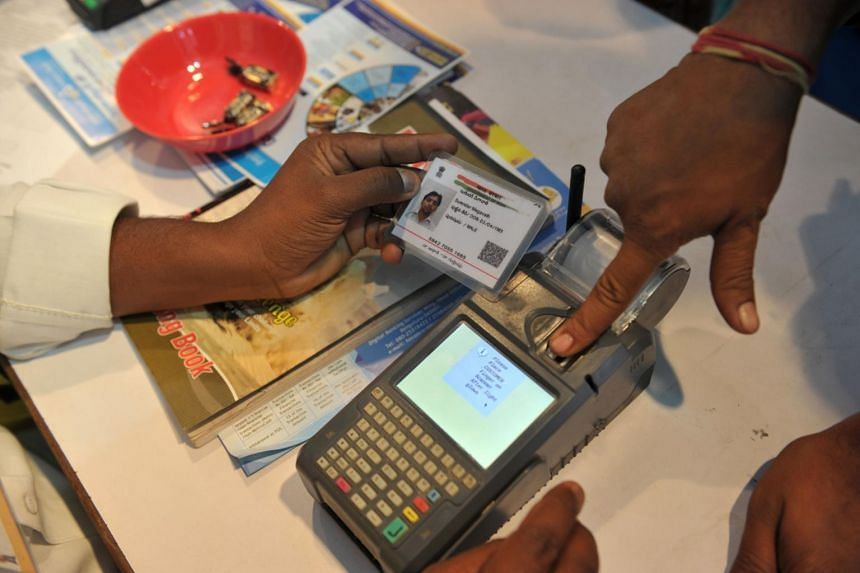 An Indian visitor giving a thumb impression to withdraw money from his bank account with his Aadhaar or Unique Identification (UID) card in Hyderabad on Jan 18, 2017.