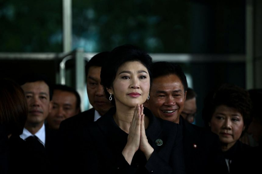 Ousted former Thai prime minister Yingluck Shinawatra greets supporters as she arrives at the Supreme Court in Bangkok, on July 21, 2017.