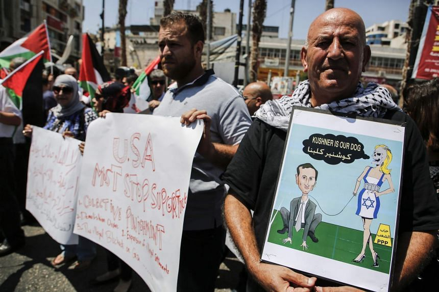 Palestinians hold a cartoon depicting Kushner as they protest against the US delegation.