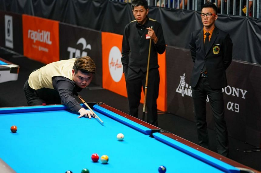 Singapore's Aloysius Yapp competing in the nine-ball pool doubles final against Myanmar's Aung Moe Thu and Maung Maung as partner Toh Lian Han looks on. Singapore won 9-3.