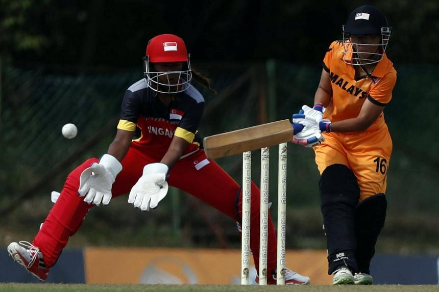 Malaysia's Christina Nina Baret playing a shot as Singapore wicket-keeper Shafina Mahesh tries for a catch during their T20 match at the SEA Games on Aug 23, 2017.