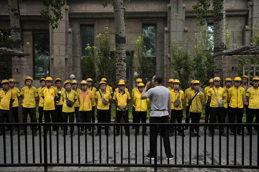 Food delivery workers (in yellow) get their morning briefing on a street in Beijing, on Aug 15, 2017.