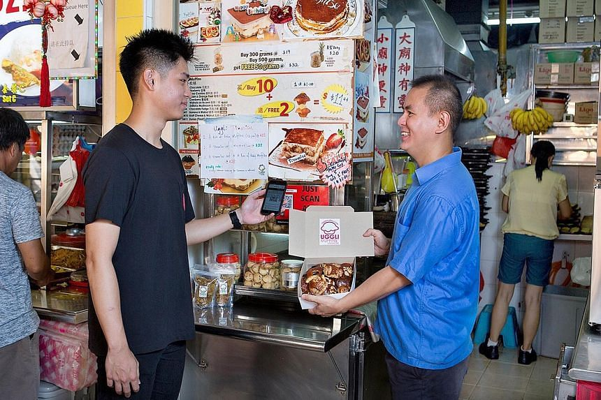 A customer using the DBS PayLah! app to pay for muffins at Uggli Muffins in Toa Payoh. The e-payment solution for the heartland should be interoperable with other payment schemes, the four government agencies say.