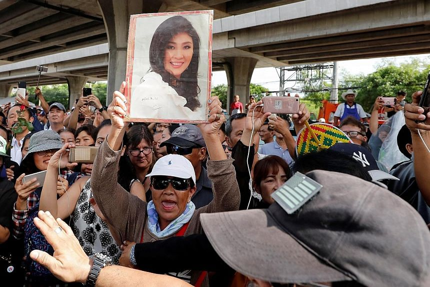 Above: Former commerce minister Boonsong Teriyapirom was sentenced to 42 years in jail yesterday for faking a government- to-government sale deal involving rice from state stockpiles. Left: Supporters of ousted former Thai prime minister Yingluck Shi