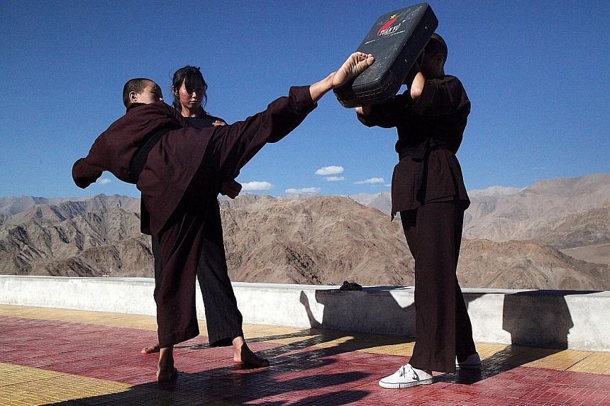 Buddhist nuns packing a punch (left) and helping participants stretch their muscles (below) during a gongfu workshop.