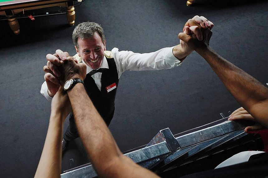 Singapore's Peter Gilchrist receiving congratulations after winning billiards gold yesterday.