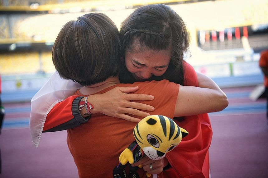 Singapore high jumper Michelle Sng sharing a hug with her coach Chan See Huey after the victory ceremony yesterday.
