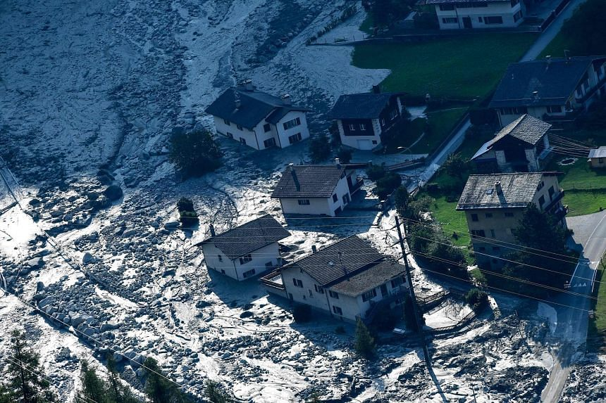 This photograph taken yesterday shows the mass of rocks and mud that slammed into buildings in the Swiss Alps village of Bondo two days earlier. A search and rescue operation is under way for the eight missing people who were hiking in the Val Bondas