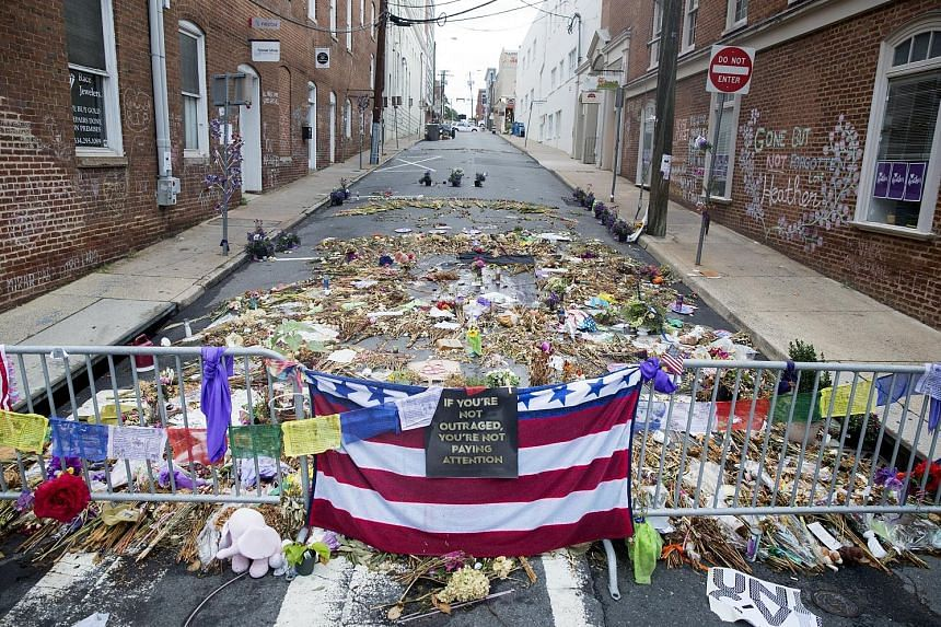 """Tributes placed in memory of Ms Heather Heyer at the site in the US city of Charlottesville where a car rammed into a crowd, killing her. Citing the episode, Mr K. Shanmugam said societies cannot just look to """"debate and discussion"""" to build and main"""